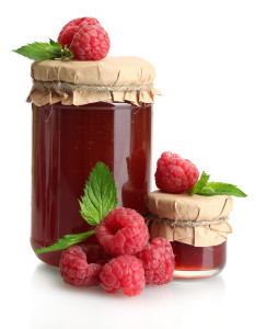 jars with jam and ripe raspberries with mint isolated on white